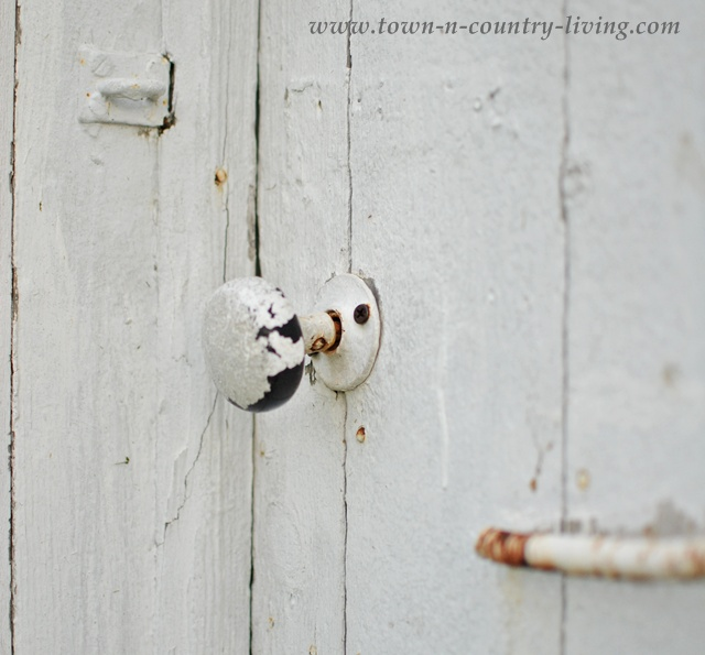 Rustic door on a shabby white outhouse
