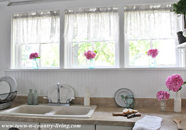 Lace valances in country kitchen windows via Town and Country Living