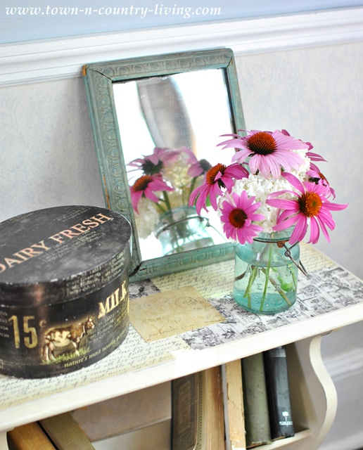 Summer flowers in a blue atlas jar atop a decoupaged end table via Town and Country Living