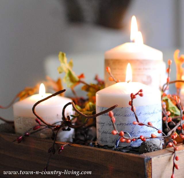 Candles create a fall centerpiece via Town and Country Living