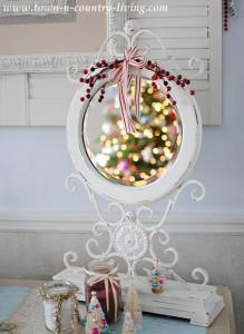 White ornate desktop mirror reflecting Christmas lights