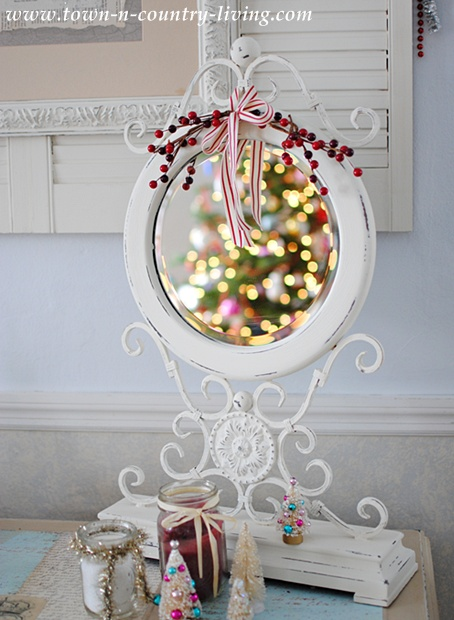 White ornate desktop mirror reflecting Christmas lights