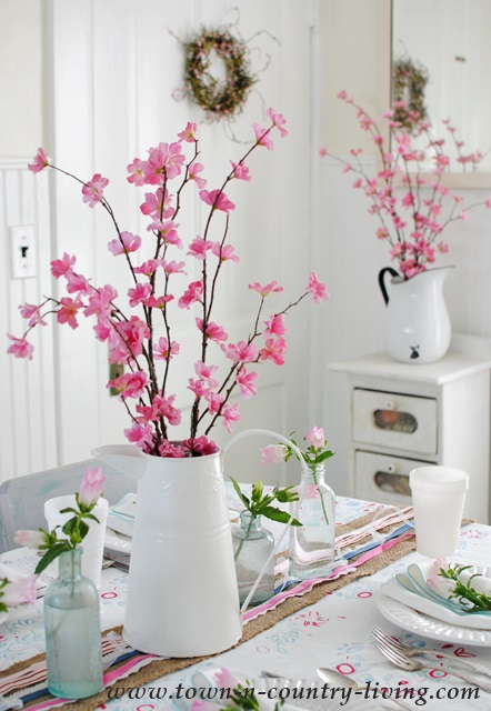 Spring blossoms in white enamelware pitchers