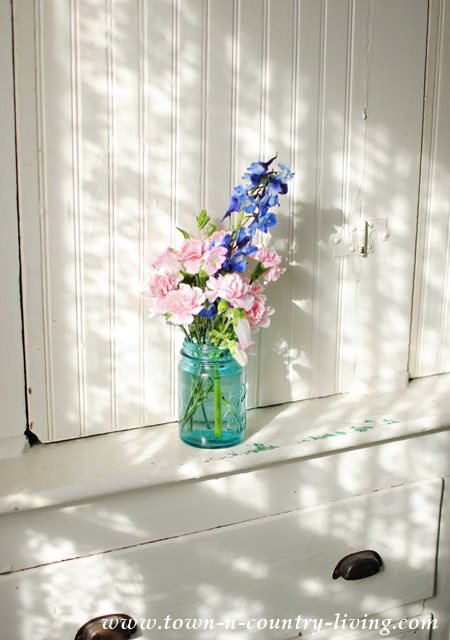 Pink and blue blooms in an aqua mason jar