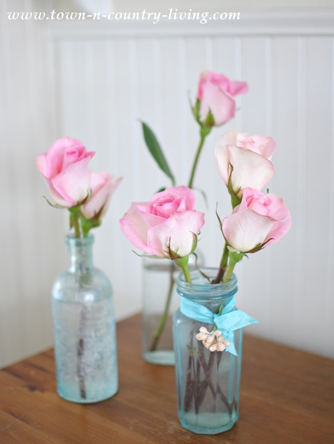Decorating with pink flowers town country living single stem pink roses in vintage aqua bottles mightylinksfo