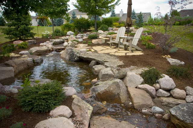 Outdoor living with water gardens town country living for Backyard streams and waterfalls