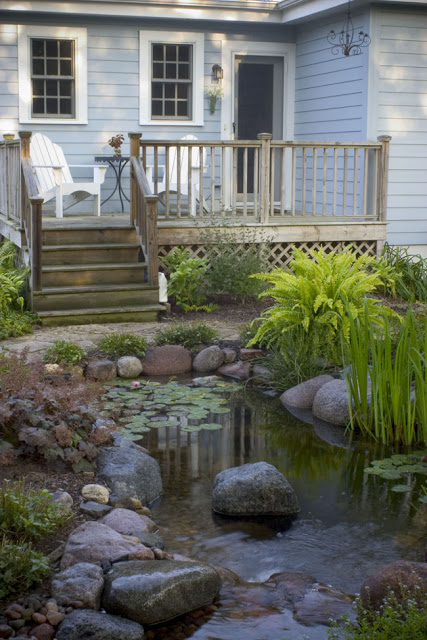 Outdoor living with water gardens town country living for Garden decking with pond