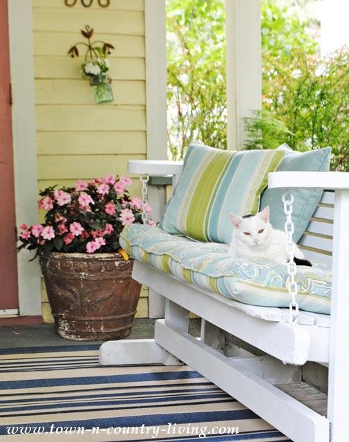 Porch Glider and New Guinea Impatiens on a Farmhouse Porch