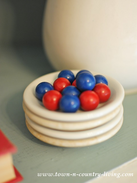 Red and Blue Wooden Marbles on White Ironstone Butter Pats