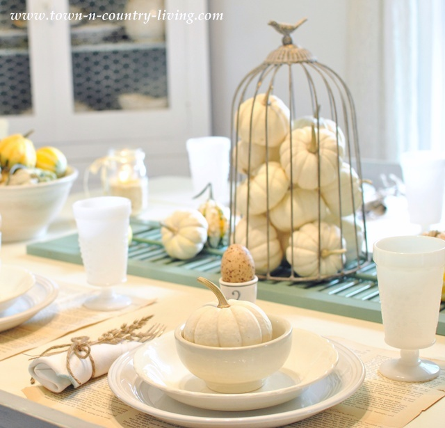 DIY Home Decor - Baby Boos in a wire cloche sit atop an old shutter and takes center stage on a Fall tablescape