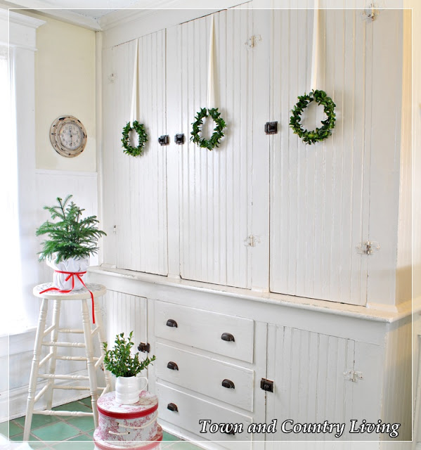 DIY Home Decor. A trio of boxwood wreaths adorns a built-in cupboard in an old farmhouse.