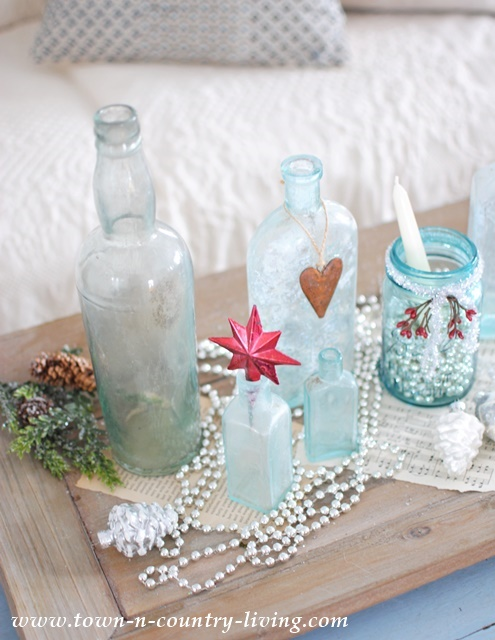 DIY Christmas Decor - create a vignette with vintage aqua bottles, touches of red, and silver glass bead garland