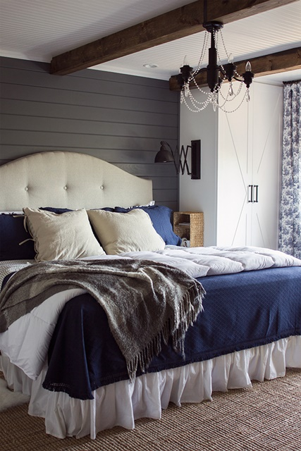 Eclectic master bedroom with planked walls and chandelier