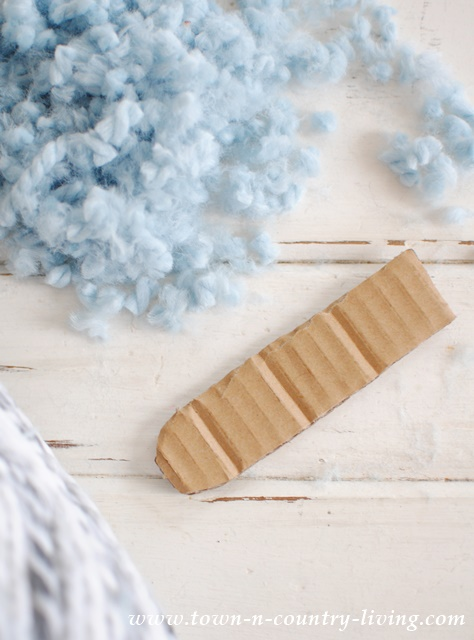 Instead of using a slippery fork to make pom poms, cut a piece of cardboard with a rounded end. The rounded end makes it easier to slip the yarn off.