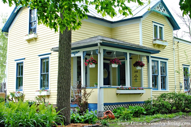 Yellow Farmhouse in Mid-Spring with Flowering Baskets