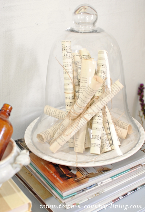 Spring Decorating. A glass cloche holds rolls of sheet music and book pages.