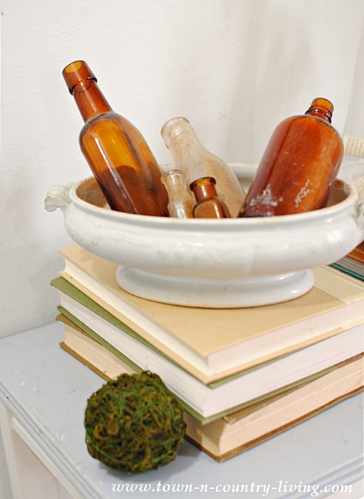 Decorate with the Unexpected. Brown bottles take up residence in a vintage white ironstone tureen.