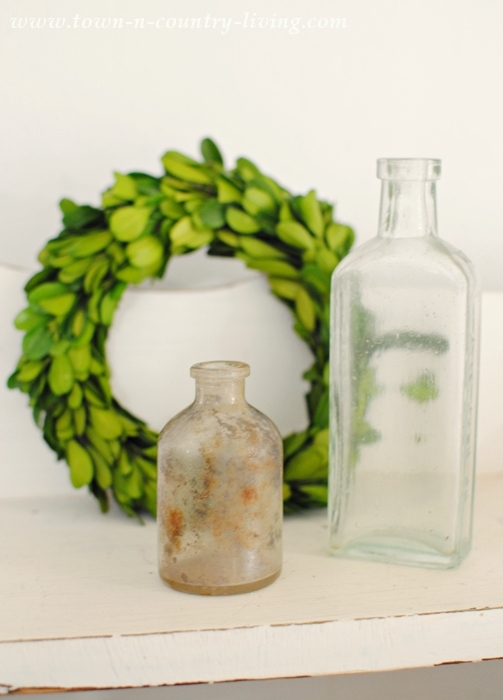Spring Vignette with Boxwood Wreath and Vintage Bottles