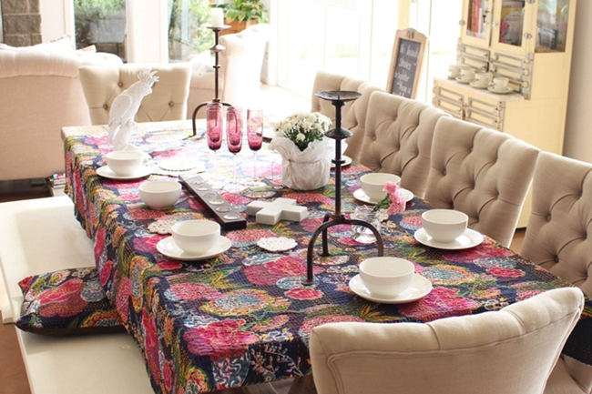 an elegant neutral dining room comes alive with a colorful quilt as a