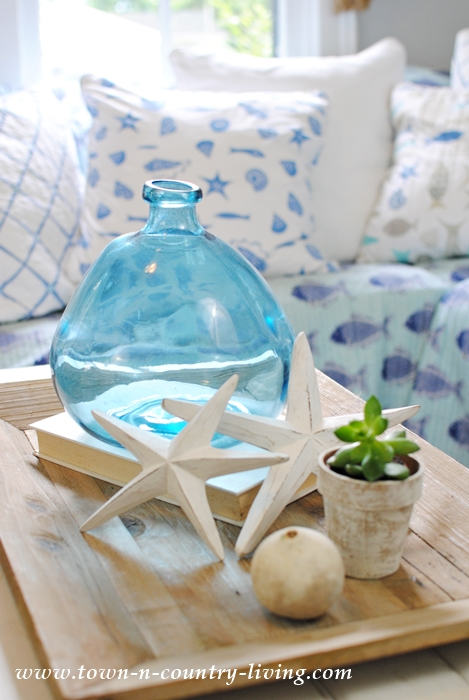 Coastal Style Vignette with Blue Glass Jar and White Wooden Starfish