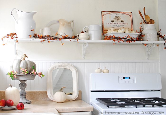 Bittersweet garland decorates open kitchen shelving with white ironstone