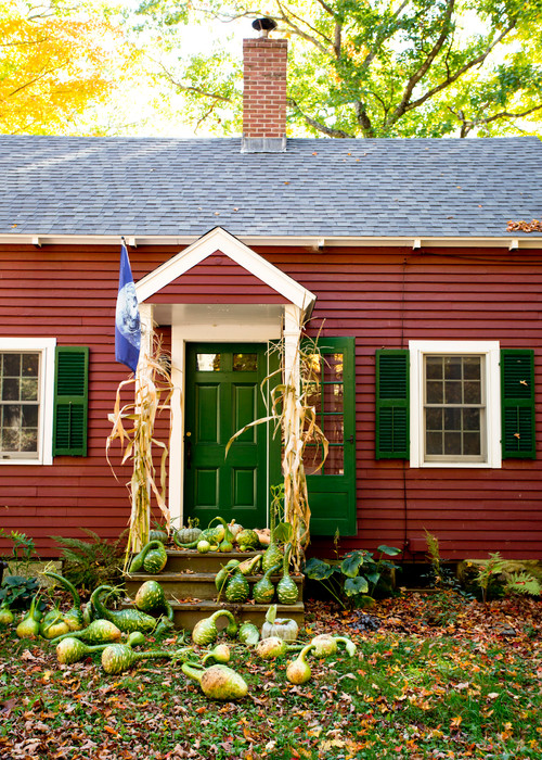 Charming Red Cottage with Green Gourds and Pumpkins