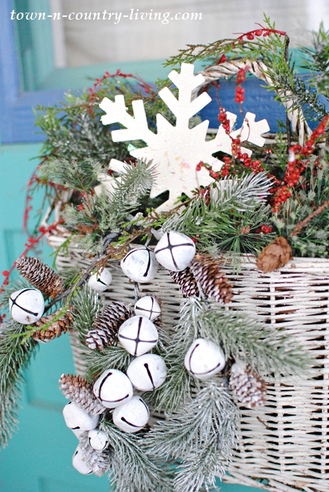 Evergreens and Jingle Bells Tucked in a Wicker Basket Adorn a Front Door at Christmas