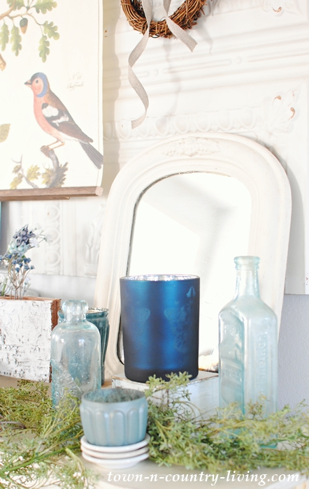 Winter Mantel Details. Candles, Mirrors and Vintage Bottles