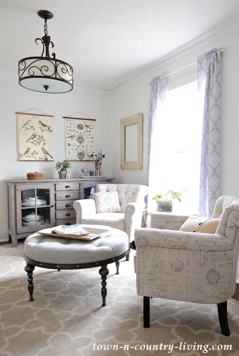 Farmhouse living room, family room, sitting room, neutral decorating, botanical prints, pendant light, tufted ottoman, script chairs, trellis rug