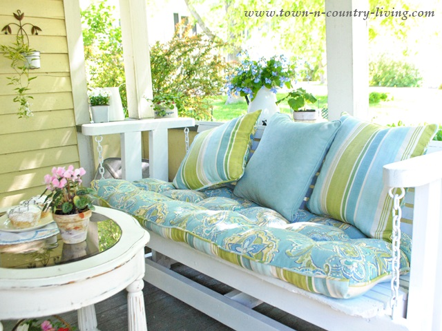 front porch swing, farmhouse porch, blue and green pillows, porch furniture