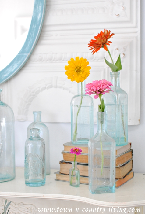 decorating with flowers, vintage aqua bottles, zinnias, flower arrangements, summer mantel