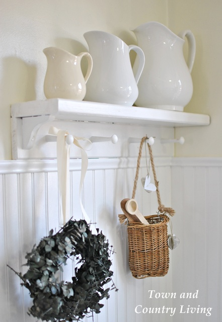 Trio of white ironstone pitchers on a farmhouse kitchen shelf