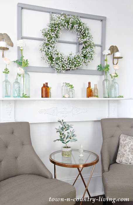 Summer mantel with vintage bottles and white flower wreath