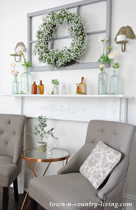 Summer mantel with vintage bottles and flowers