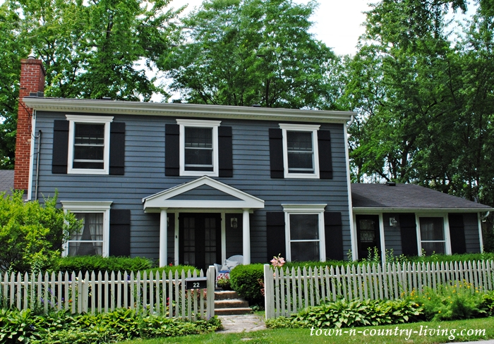 Old gray colonial home with white picket fence