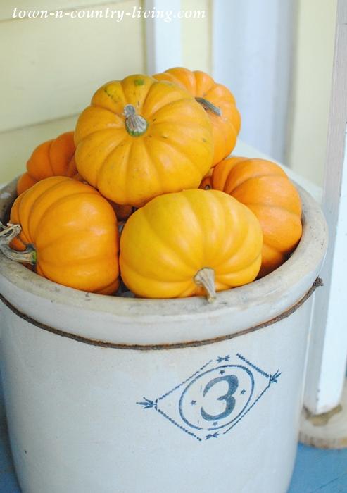 Mini pumpkins fill a stoneware crock