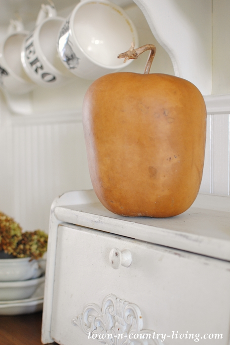 Fall foliage and dried gourds add autumn appeal to a farmhouse kitchen