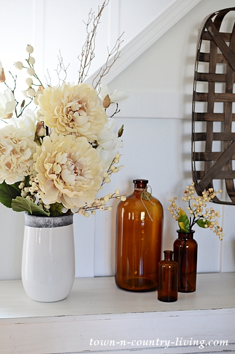 Off-White Faux Flowers and Brown Vintage Bottles