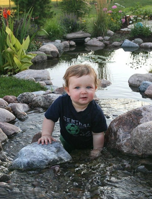 Baby Exploring a Backyard Pond and Waterfall
