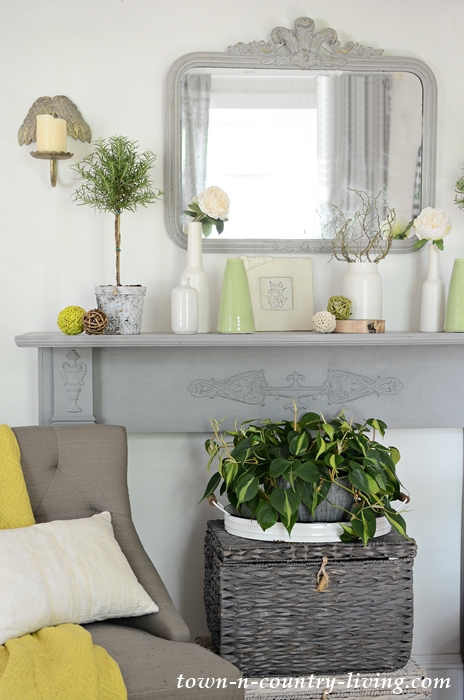 Styling a summer mantel with favorite vases and plants