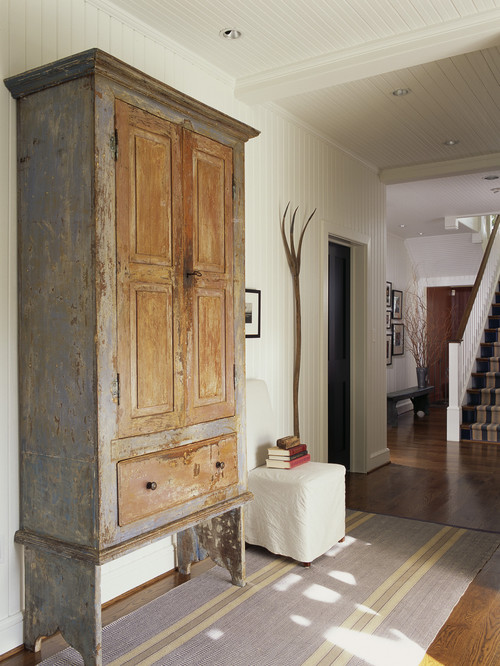 Antique armoire and primitive pitchfork in modern farmhouse entryway