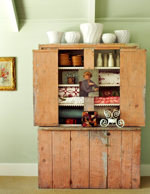 Vintage quilts and pottery displayed in rustic country cupboard
