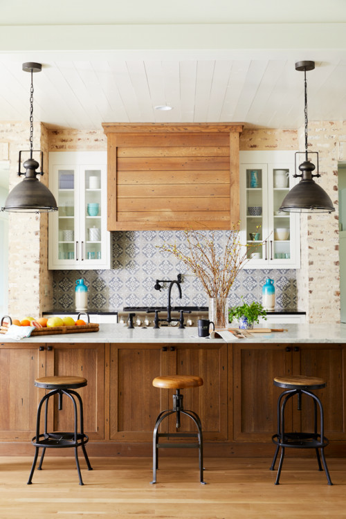 Brick walls and blue tile back splash in a rustic kitchen