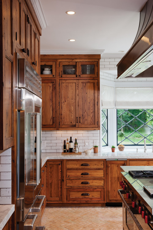 Rich Wood Grain Cabinets with White Subway Tile and Brick Floor