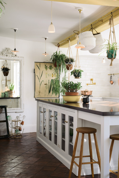 White Kitchen with Dark Tile Floors and Plenty of Houseplants