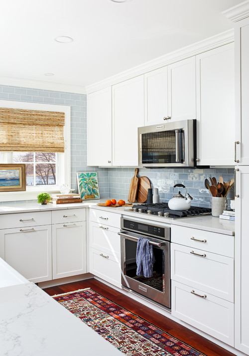 Beautiful white kitchen with pale blue subway tile