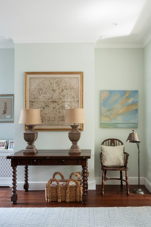 Soft colors in a living room are grounded with rich wood floors and furnishings.