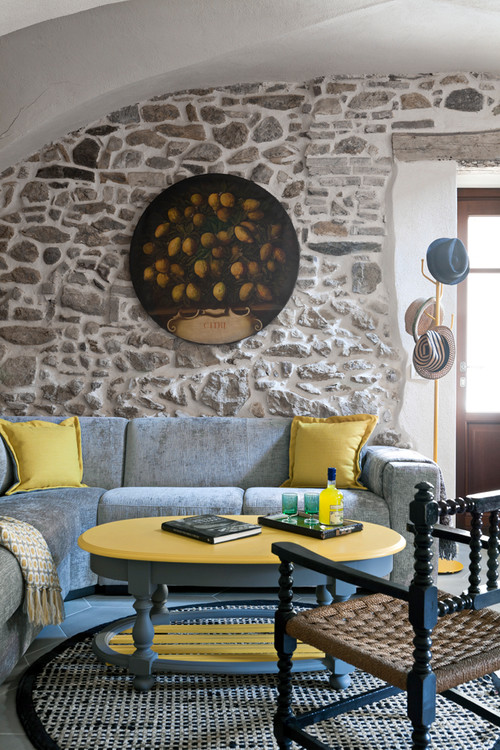 Mediterranean living room with stone wall and light blue sectional