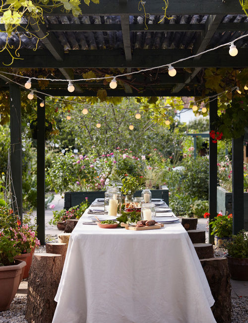 Wooden Pergola with Dining Table and String of Lights