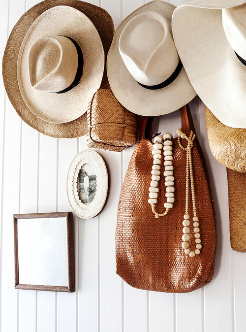 Straw hats on coat hooks in an entryway